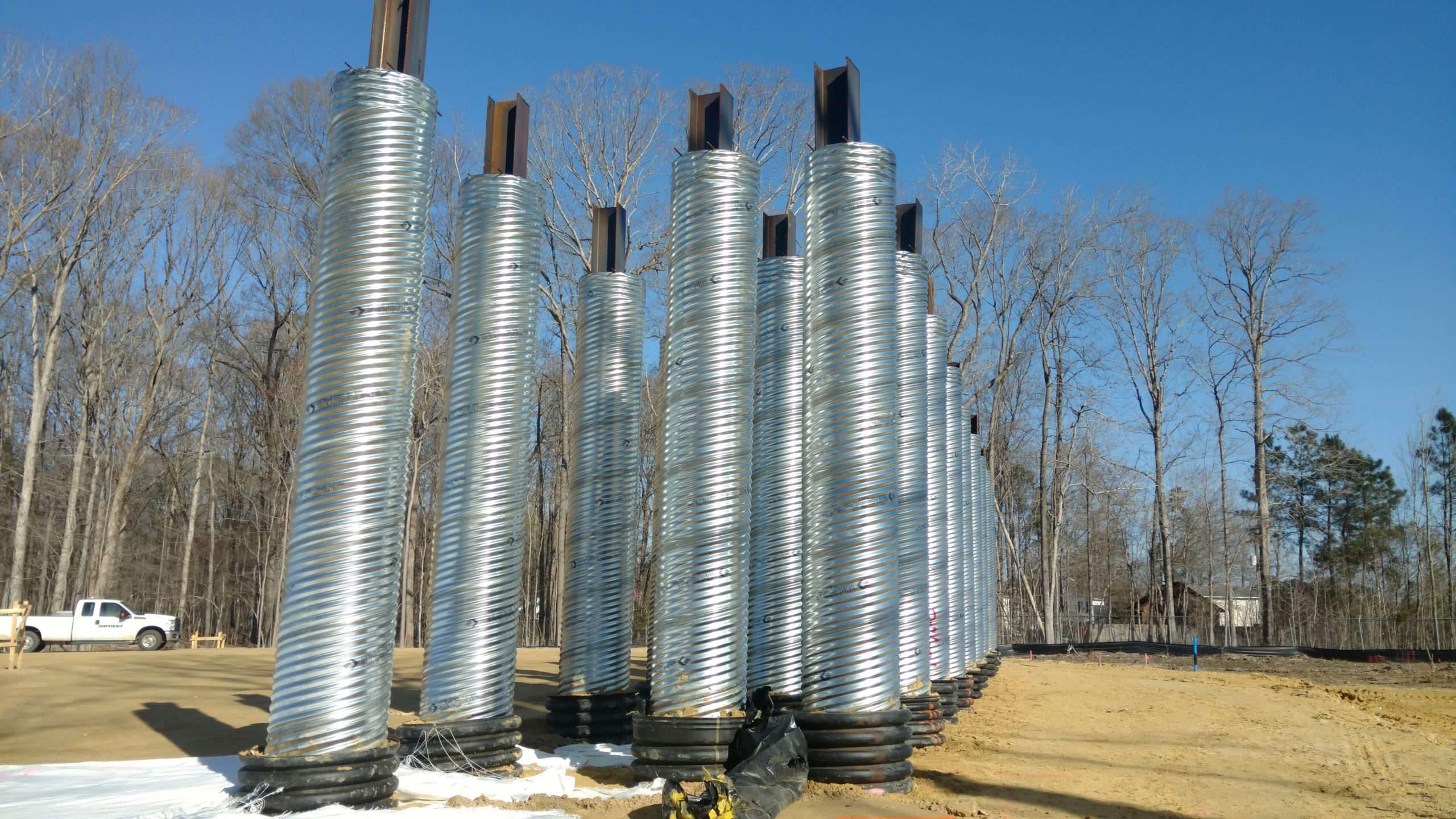 Corrugated metal pile sleeves for MSE wall construction