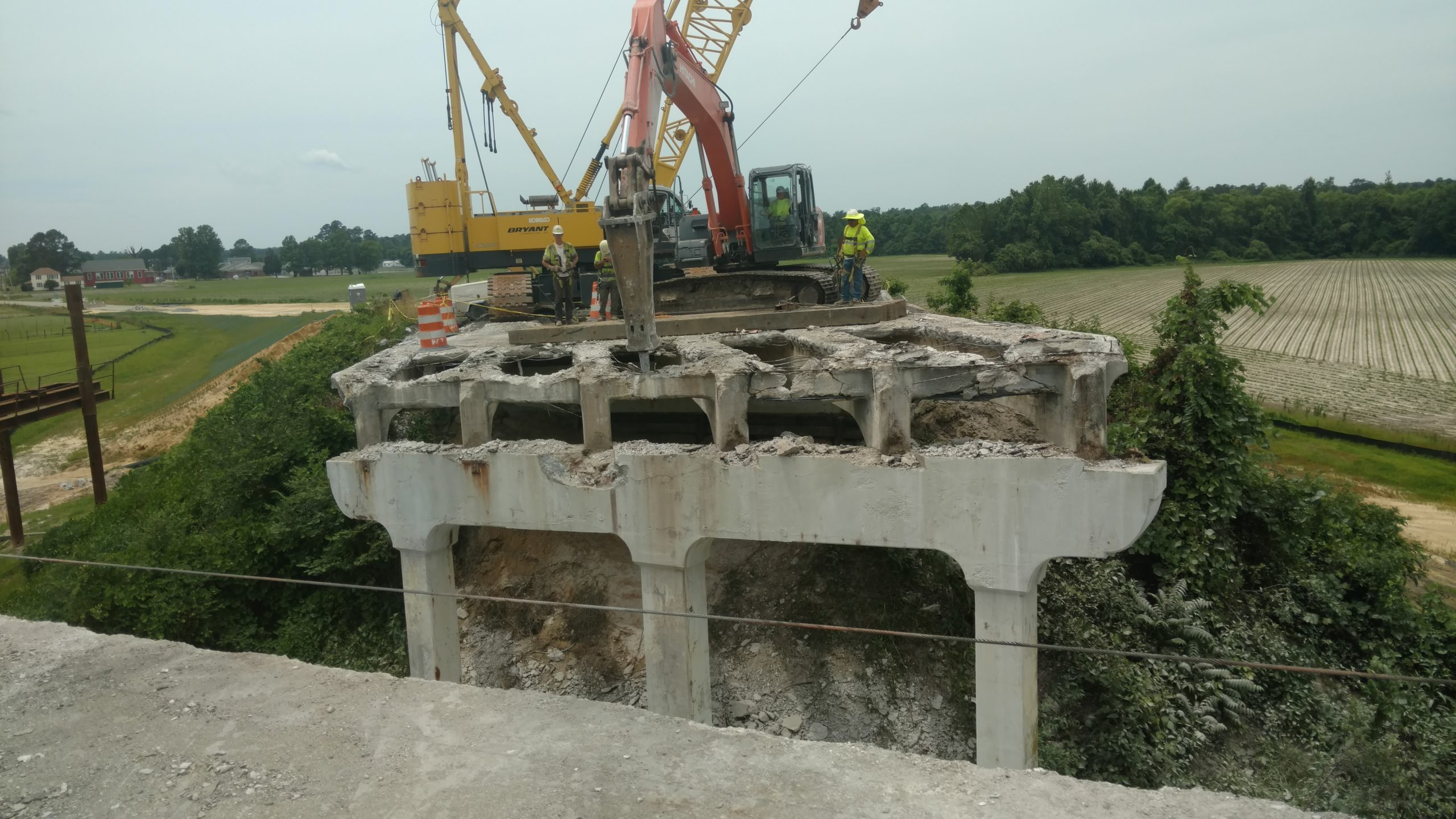Demolition of existing bridge deck with Hitachi excavator and hoe ram attachment