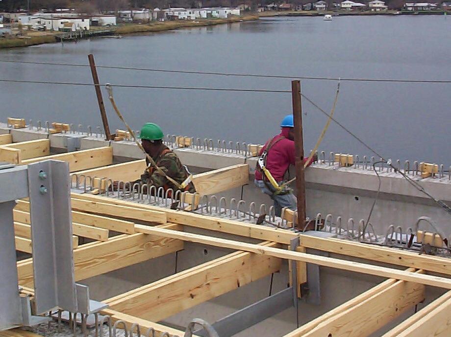 Installing wood flooring between beams for bridge deck construction